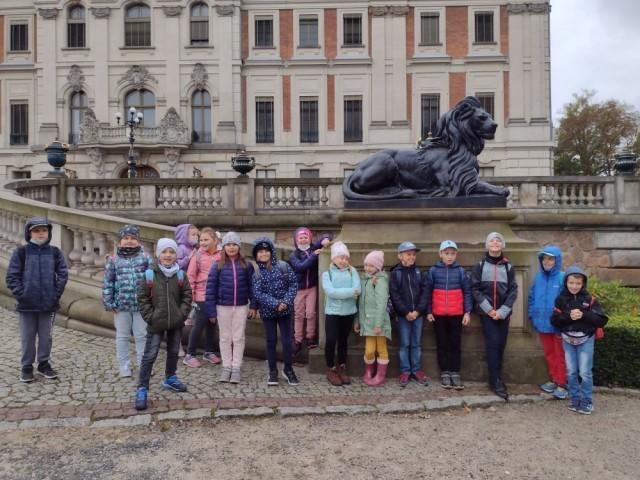 Obraz przedstawia uczniów przed zamkiem