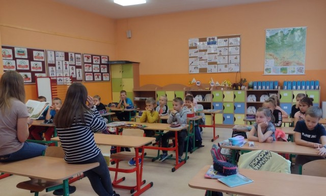 Obraz przedstawia uczniów słuchających głośnego czytania